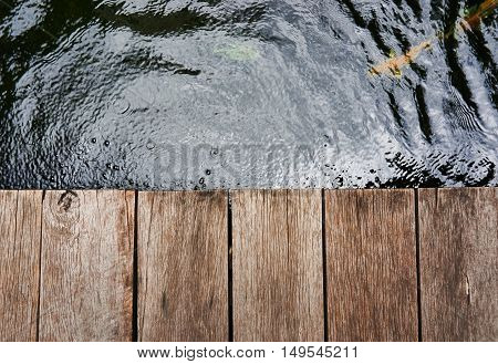 Wooden board empty table over the pond.