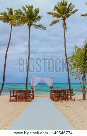 Wedding preparation on caribbean beach against a background of palms and beautiful sea. Punta Cana Dominican Republic.
