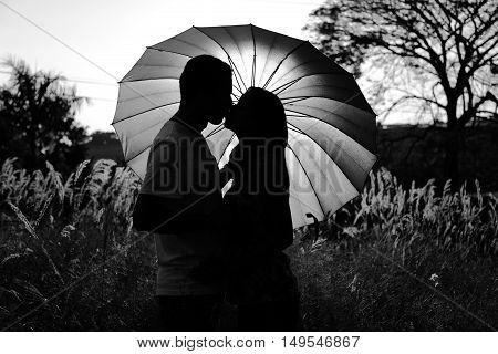 Silhouette of a romantic couple kissing in front of an umbrella. Concept of love and union. Black and white picture.