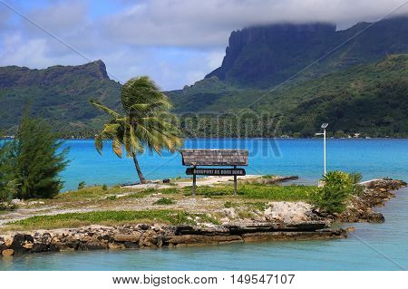 Bora Bora airport sign. Beautiful palms and blue sea at the background. French Polynesia South Pacific Ocean.