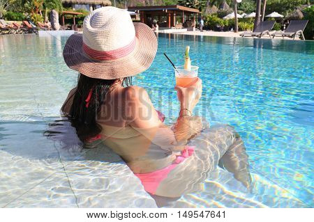 Beautiful woman using hat and bikini enjoy a tropical resort sitting front pool and drinking cocktail back view.