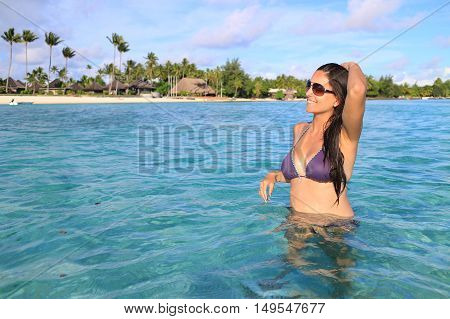 Attractive young caucasian long hair woman in purple swimsuit on the beach.