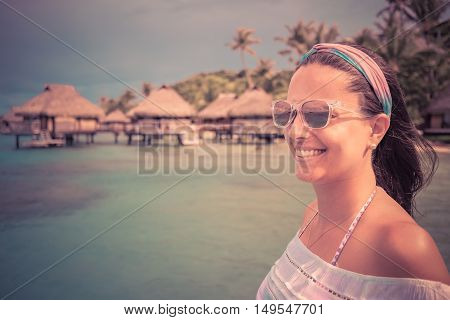 Face of smiling young woman over bungalow on beach background. Retro style color tones.