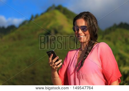 Woman smiling and using a smart phone. Green mountain in the background. Beautiful long hair and brunette girl in summer clothes