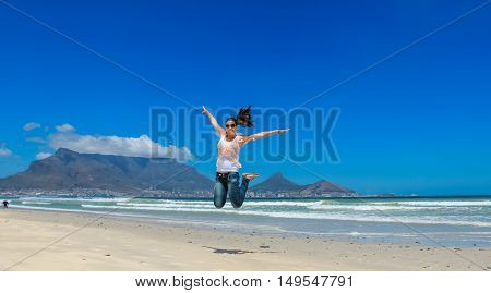Beautiful girl jumping at Milnerton beach Cape Town. Table Mountain and breaking waves in the background. Concept photo of happiness freedom and lifestyle.