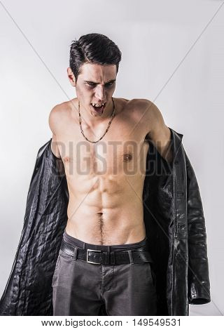 Portrait of a Young Vampire Man in an Open Black Leather Jacket, Showing his Chest and Abs, Looking at the Camera, on a Black Background.