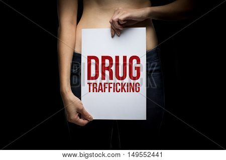 Woman with drug trafficking sign in a dark background