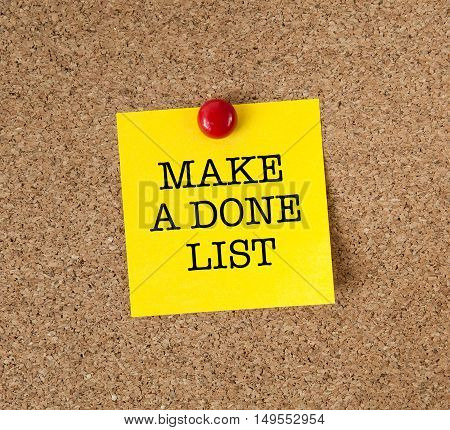 The phrase Make A Done List in red text on a yellow sticky note posted on a cork board as a source of motivation