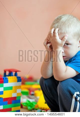 young boy sitting on the floor crying looking away
