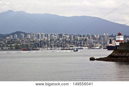 View of Brockton Point Lighthouse from the walking path in Stanley Park with ships and boats in the harbour and North Vancouver and the Rockies rising in the background.