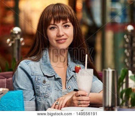 Pretty girl looking at camera and holding cup at the cafe