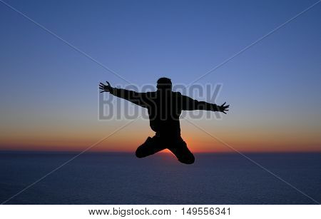 Silhouette of a man jumping in front of the sunset in the ocean. Concept photo of happiness freedom and lifestyle.