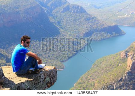 Young man sitting on stone on the cliff in the Blyde River Canyon South Africa