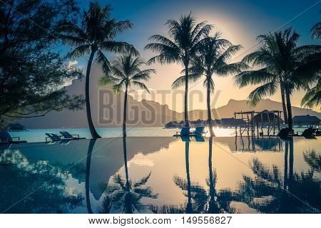 Sunset in Bora Bora French Polynesia. Palm trees and Mount Otemanu reflected in the pool. Retro style color tones.