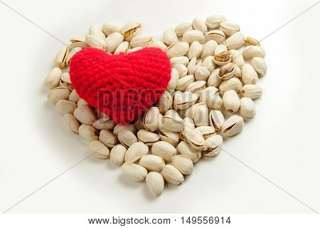 Roasted pistachio nuts with Knitting yarn to form a red heart on white background healthy food and nutrition