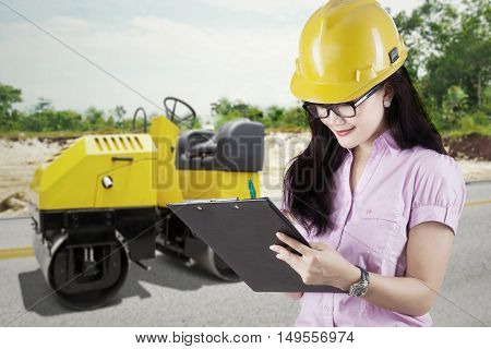 Image of young businesswoman writing on clipboard with road roller on the road