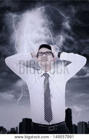 Young businessman has trouble and holding head with his hand under thunderstorm
