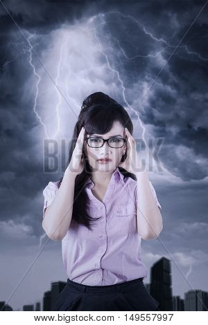 Businesswoman has trouble and her hands on head with dark cloud over her head