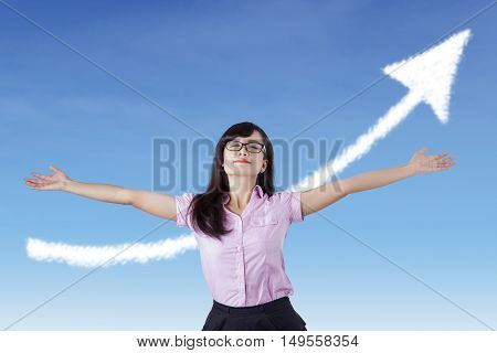 Young entrepreneur raising hand and standing in front of camera with upward arrow in the blue sky