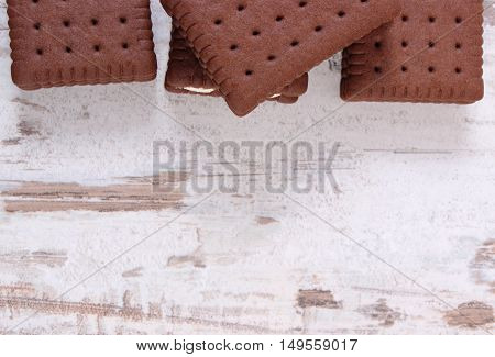 Crunchy cookies and biscuit with copy space for text on old wooden white background concept of reduction eating sweets