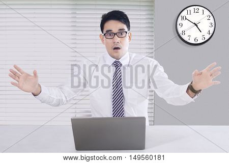 Image of handsome male shocked after look his laptop and looking at the camera office and clock in the background