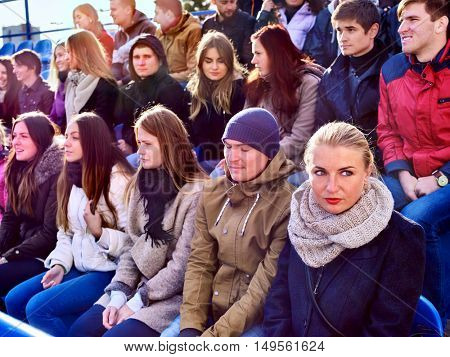 Disappointed fans on tribune. Loss of their favorite team. Sport fans Unhappy group people fans . Sad girl wearing warm scarf in foreground.