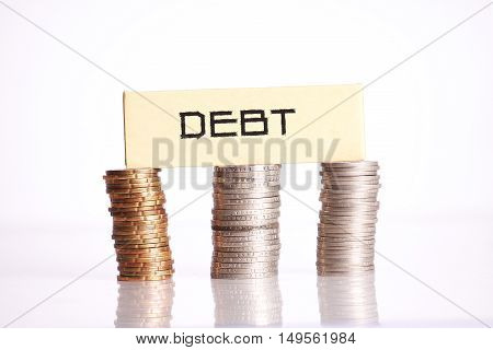Debt words on top of coins isolated on white background