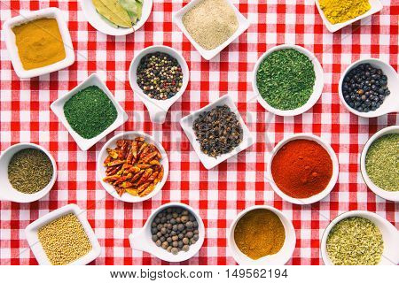 Various dried herbs and spices on checkered tablecloth. Top view.