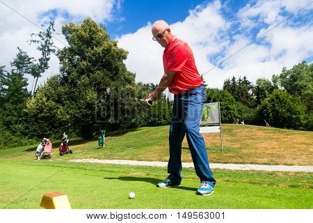 Senior man doing tee stroke on golf course