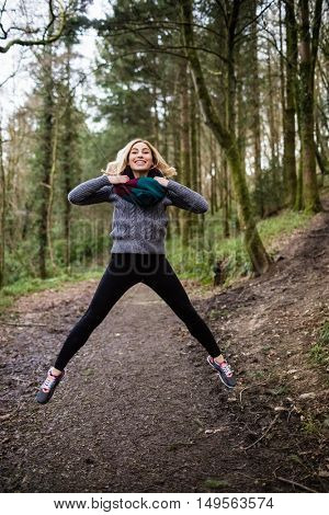 Beautiful smiling woman jumping in forest