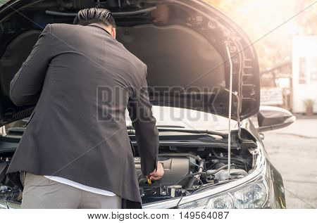 Young man trying to fix his broken down car on the side of the road. Open the hood broken car see engines that damaged or not.