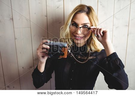 Portrait of woman posing with camera and spectacle against texture background