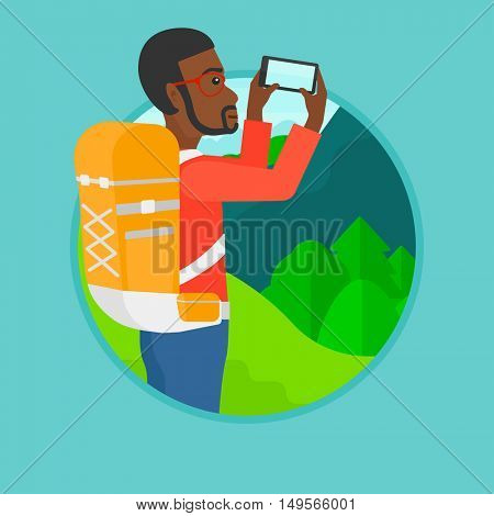 An african-american man taking photo of landscape with mountains. Young tourist with backpack taking photo with his cellphone. Vector flat design illustration in the circle isolated on background.