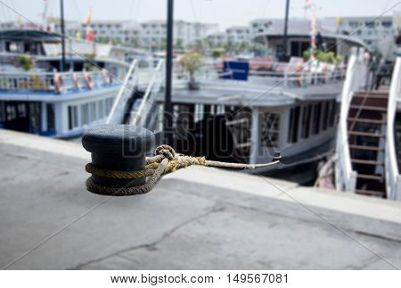 Mooring rope with a knotted tied around a cleat with tour boat at the pier