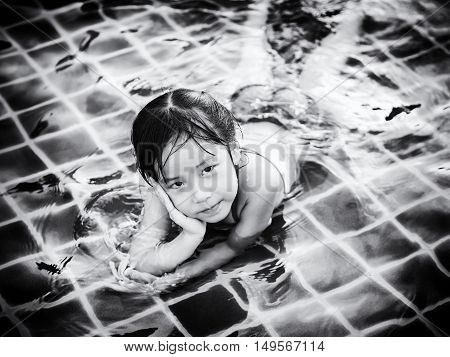Asian girl is playing in the pool laying down black and white