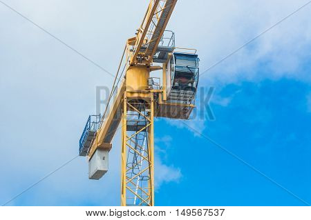 Part of a construction crane against blue sky photographed space for labeling.