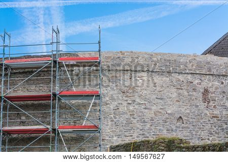 Old castle wall with scaffolding against blue sky.