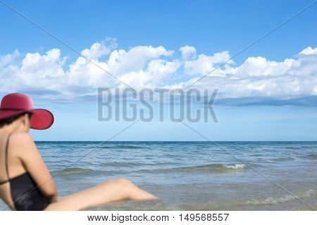 Blurred woman in pink beach hat relaxing in the sea with blue sky and white cloud