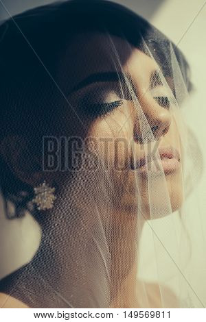 Beautiful bride woman with eyes closed under veil dreams on sunny day isolated on white