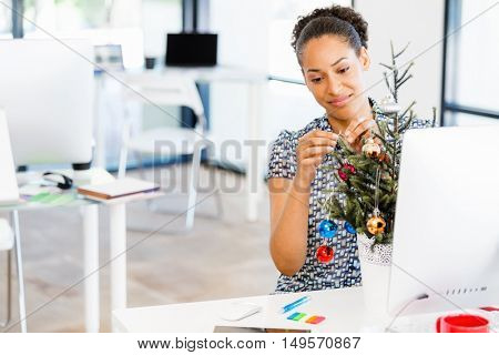 Portrait of smiling female office worker with Christmas tree