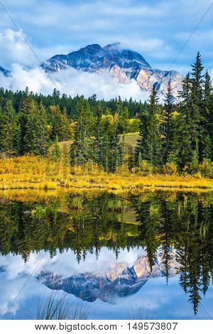 Patricia Lake amongst the evergreen forests, yellow bushes and mountains. Autumn in the Rocky Mountains of Canada