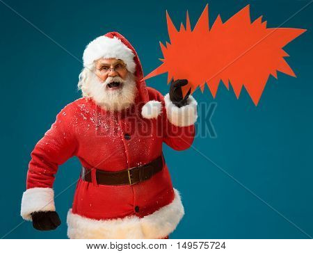 Resentful Santa Claus showing sign speech bubble banner looking angry and nervous. Irritated Santa Claus on blue background