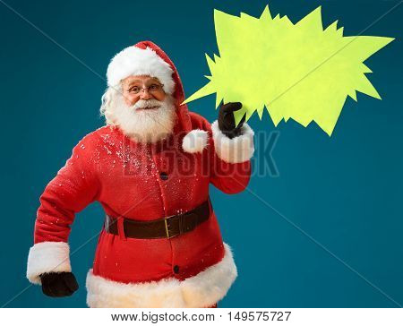 Smiling Santa Claus showing sign speech bubble banner looking happy excited. Happy Santa Claus on blue background having idea