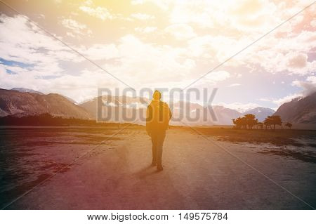 Silhouette Of Male Traveler With Backpack Walking Against The Sunlight In Mountain Highland Area