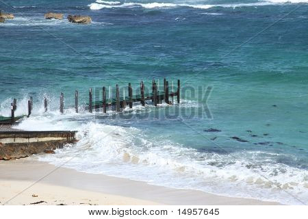 Wooden pier on beach with choppy blue seas