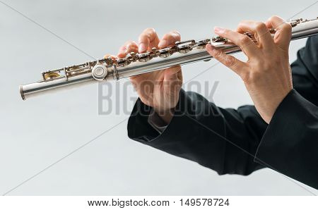 Professional elegant female flutist performing in a white room hands close up