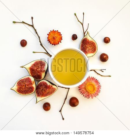 Bright morning cup of tea with fig fruits. Autumn decoration: yellow dry flowers chestnuts and tree branches. Flat lay top view view from above