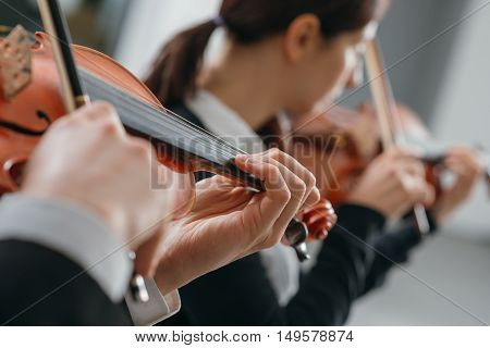 Two violinists performing together hands close up classical music concert