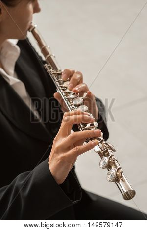 Elegant woman playing a transverse flute classical music professional