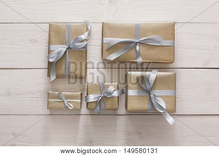 Top view of Gift boxes on white wood background. Presents in craft paper decorated with stylish elegant silver satin ribbon bows. Christmas and any other holidays concept, top view, flat lay